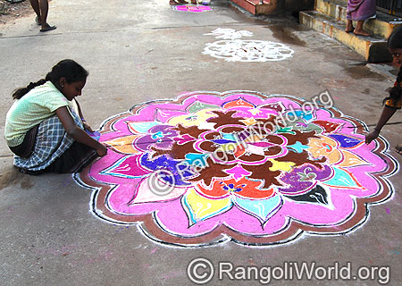 Little Girl Giving Colors to Freehand Rangoli